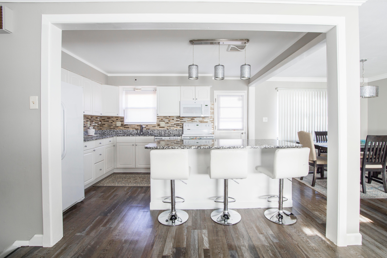Tiszta parkettás konyha,fehér bútorokkal.